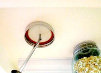 Na spodnjo stran visečih omaric pritrdite pokrovček kozarca za vlaganje – zanimiv način shranjevanja.